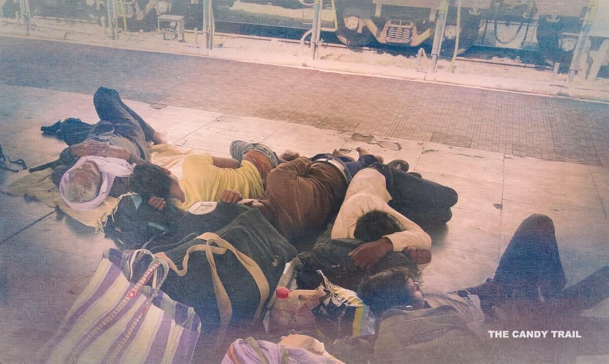 men sleeping on platform of railway station in india.