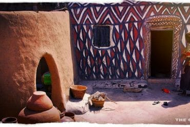 woman painted house courtyard sirigu ghana
