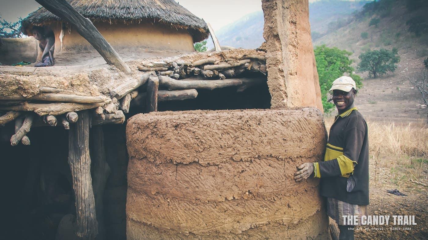 man rebuilding mud house tamberma valley togo