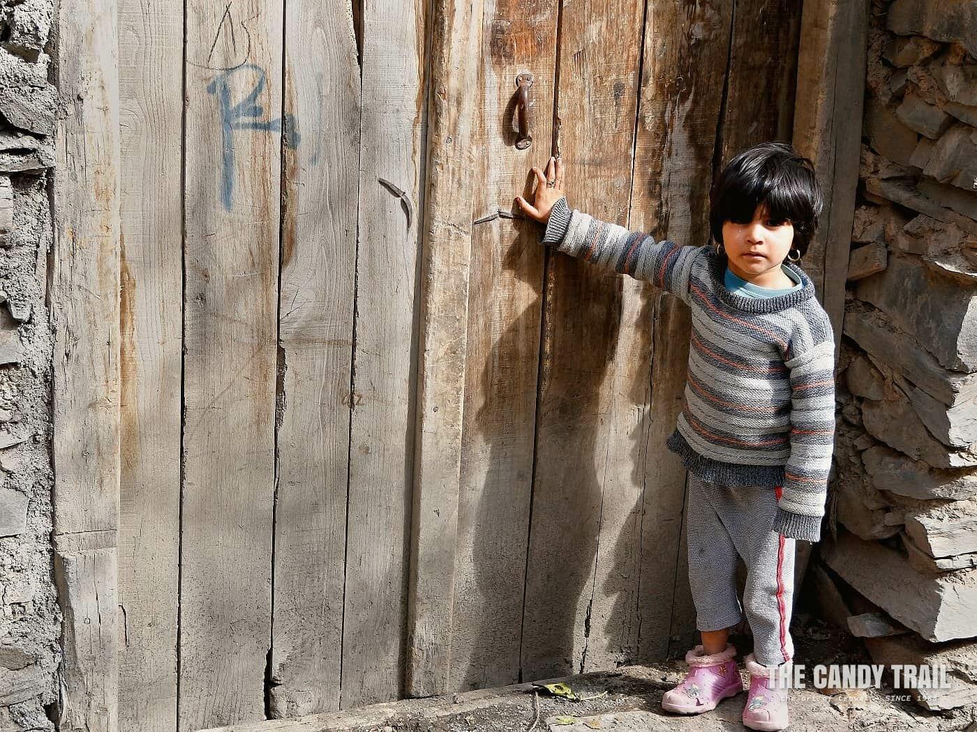 young girl at door kang village iran