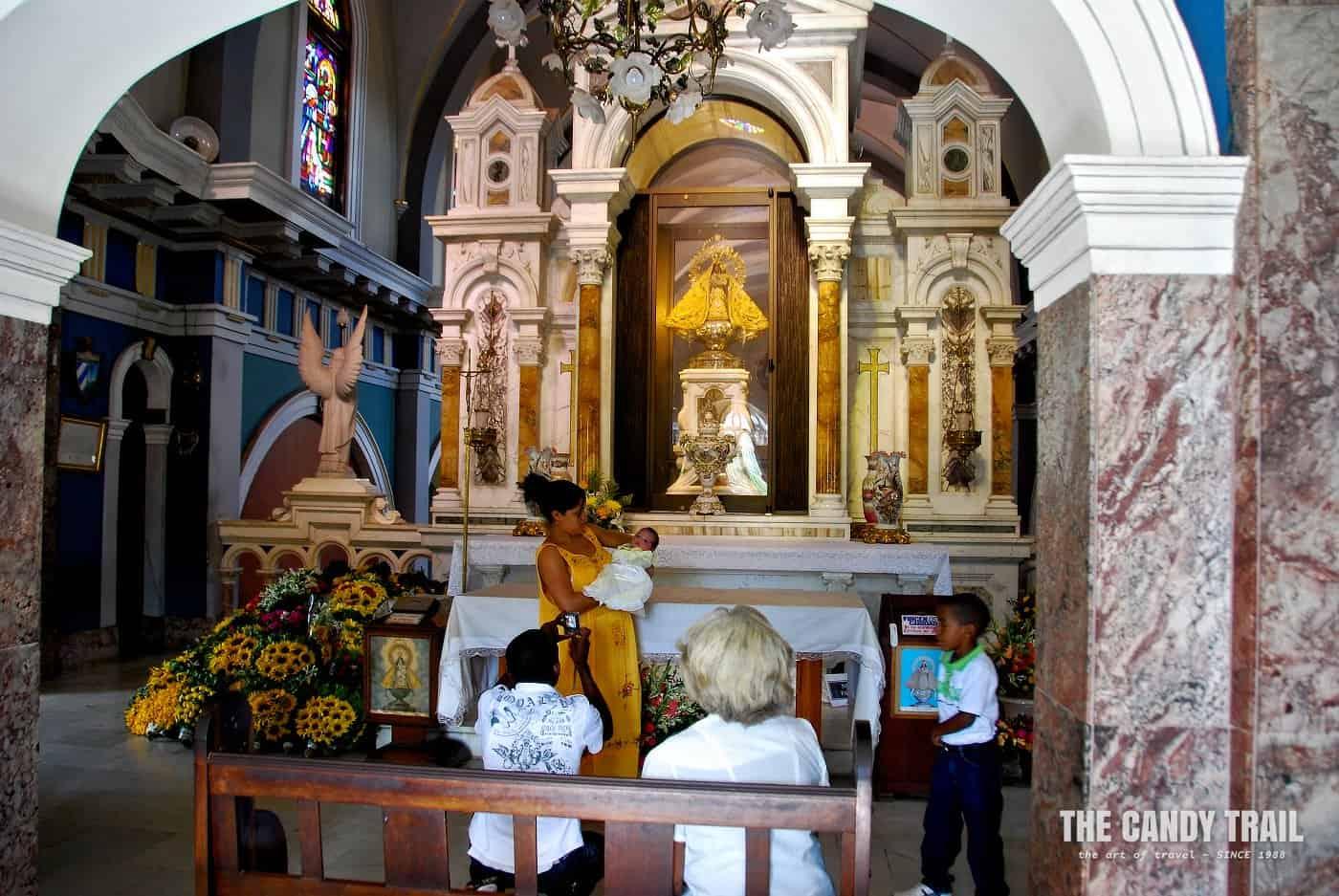 Family with baby pose at the altar of Basilica de Nuestra Señora del Cobre