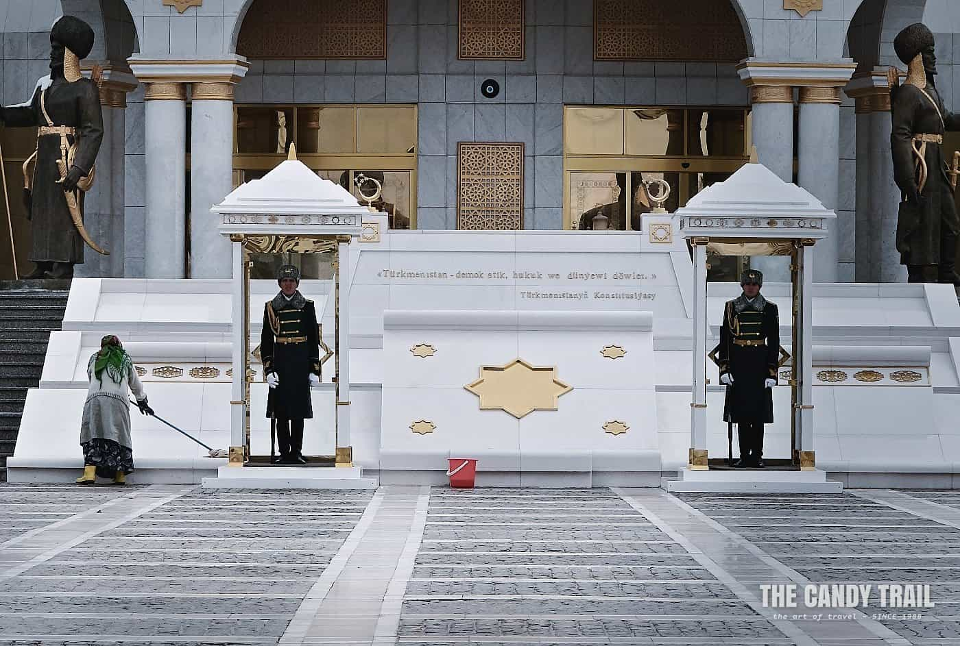 Guards at Independence monument in their sentry boxes and women cleans the marble around them ashgabat turkmenistan